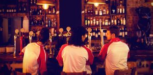 jersey pub 300x148 - Group of male friends sitting at counter in pub